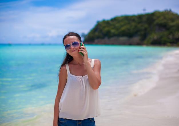 彼女の電話で話しているビーチでクローズアップ若い美しい女性
