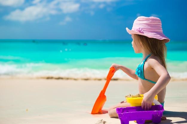 Прелестная маленькая девочка играя на пляже с белым песком