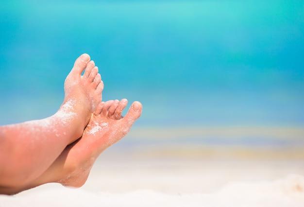 白い砂浜で女性の足のクローズアップ