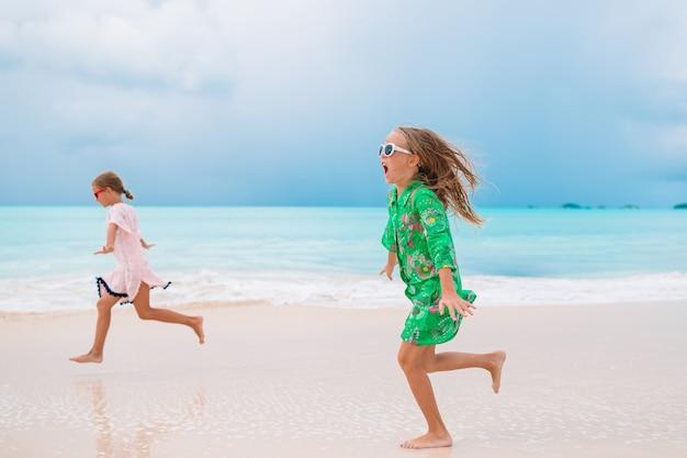 熱帯のビーチでの休暇を楽しんで楽しんでいる小さな女の子