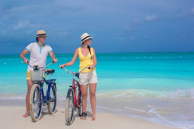 Молодая счастливая пара езда на велосипеде на белом тропическом пляже