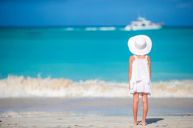 ビーチで大きな赤い帽子の愛らしい少女