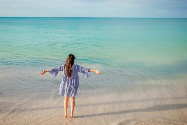 Молодая модная женщина в зеленом платье на пляже