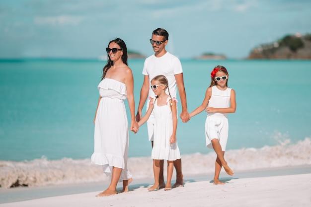 Счастливая красивая семья из четырех человек на белом пляже