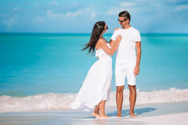 Молодая пара прогулки на тропическом пляже с белым песком и бирюзовой океанской водой на острове антигуа в карибском бассейне