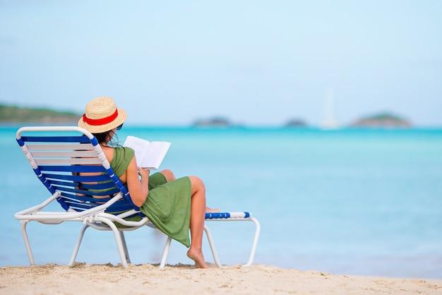 若い女性は、ビーチの長椅子で本を読んで
