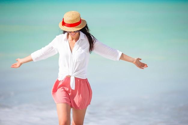 ビーチで帽子の若者のファッション女性