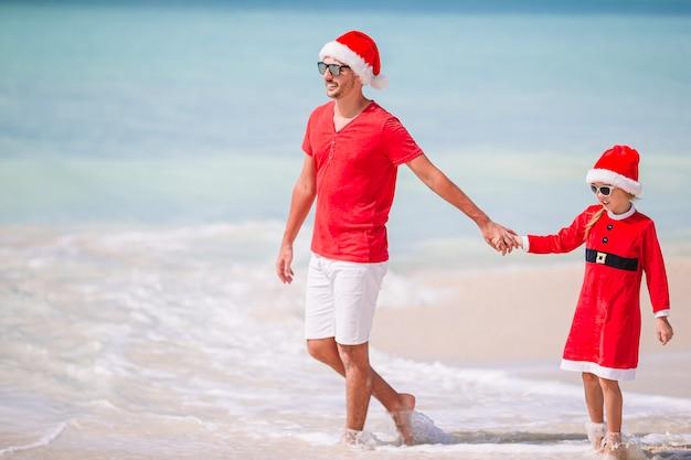 サンタ帽子の父と娘は、熱帯のビーチで楽しい時を過す