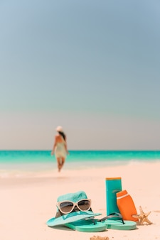 サンクリームボトル、サングラス、白い砂の背景海にビーチサンダル