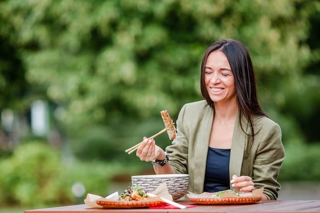 Молодая женщина ест забрать лапшу на улице