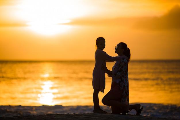 Маленькая девочка и счастливая мать силуэт на закате на пляже