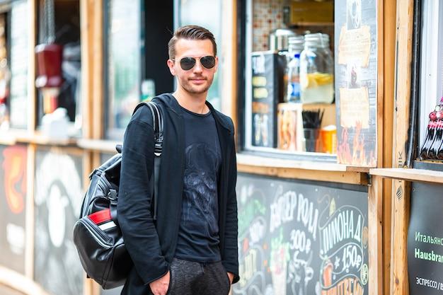 屋外のストリートフードマーケットのバックパックと若い男