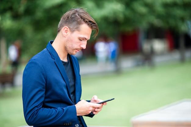 Человек читает текстовое сообщение на мобильном телефоне во время прогулки в парке