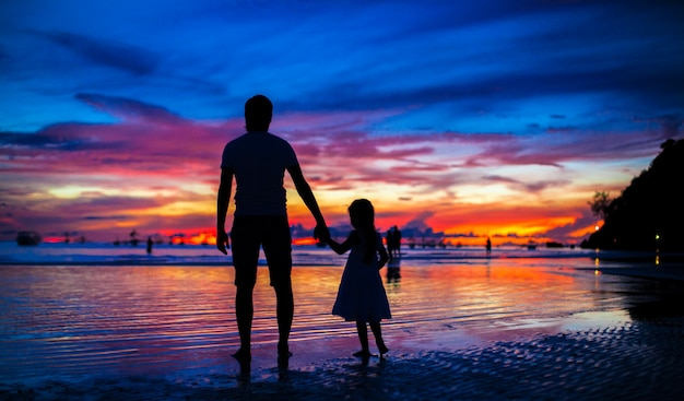 Отец и дочь силуэты в закат на пляже на боракае