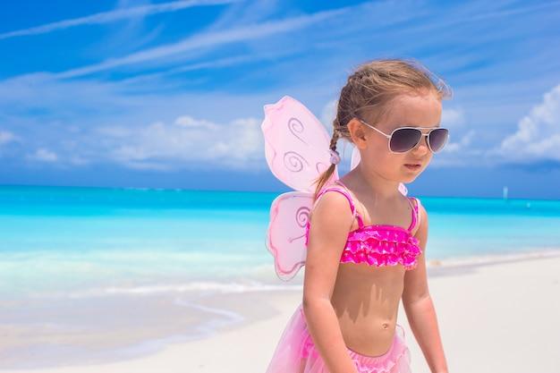 Очаровательная маленькая девочка с крыльями как бабочка на пляжном отдыхе