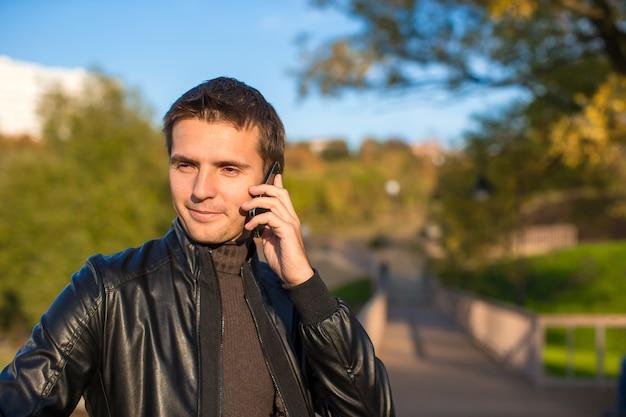 公園で携帯電話を持つ若者