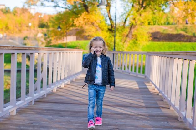 Очаровательная маленькая девочка в теплый осенний день на открытом воздухе