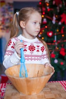 キッチンでクリスマスのジンジャーブレッドクッキーを焼く少女