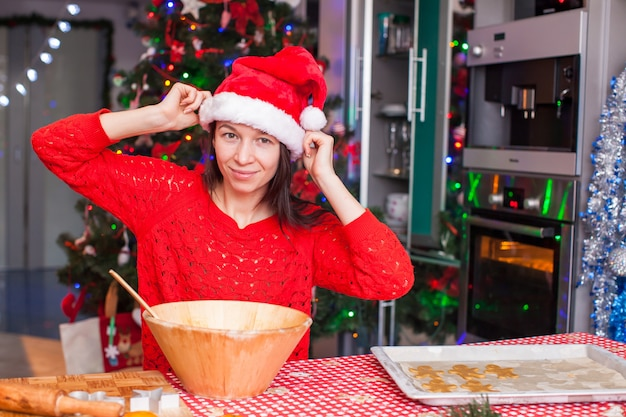 赤いクリスマス帽子の若い女性が自宅で親指を立てた
