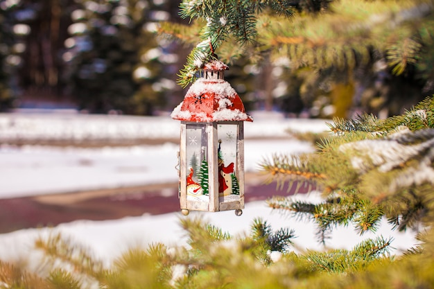 Декоративный рождественский фонарь на еловой ветке в снежный зимний день