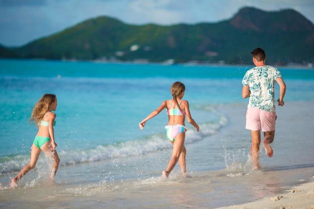 父とビーチで夏休みを楽しんでいる子供たち