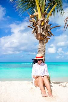 熱帯の白いビーチの中に本を読む若い女性