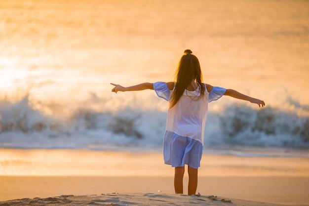 夕暮れ時の白いビーチの上を歩いて愛らしい幸せな女の子。