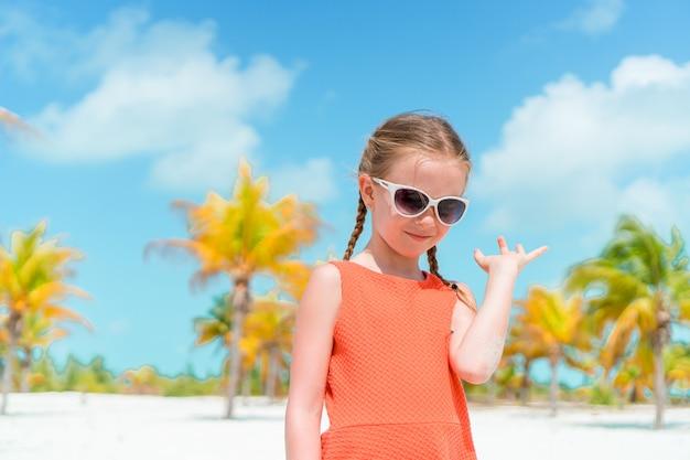 Милая маленькая девочка на пляже во время карибских каникул