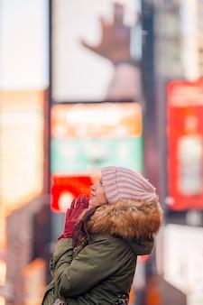 タイムズスクエアの観光客またはニューヨーク、マンハッタン、ニューヨーク、アメリカを訪れる若い幸せな女性としてのニューヨーク市の女性。