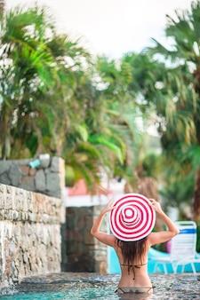 Красивая молодая девушка расслабляющий в бассейне на открытом воздухе