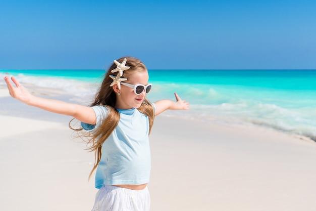 楽しいビーチでドレスの美しい少女。面白い女の子は夏休みをお楽しみください。