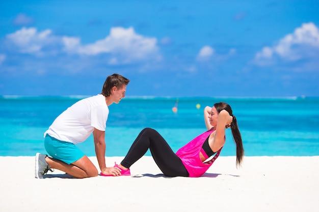 若いカップルは休暇中に白いビーチで腹部のクランチを行います
