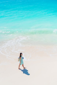 浅瀬でたくさんの楽しみを持っているビーチで幸せな女の子