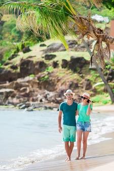 夏休みの間に白いビーチで若いカップル。幸せな家族が新婚旅行を楽しむ
