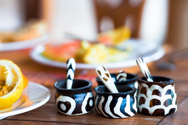 Шейкеры с солью и перцем из африканских стран на завтрак в ресторане на открытом воздухе