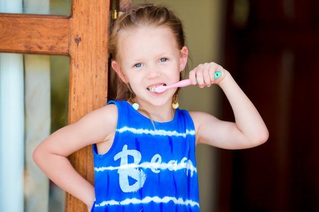 Гигиена полости рта. очаровательная маленькая улыбающаяся девушка чистит зубы