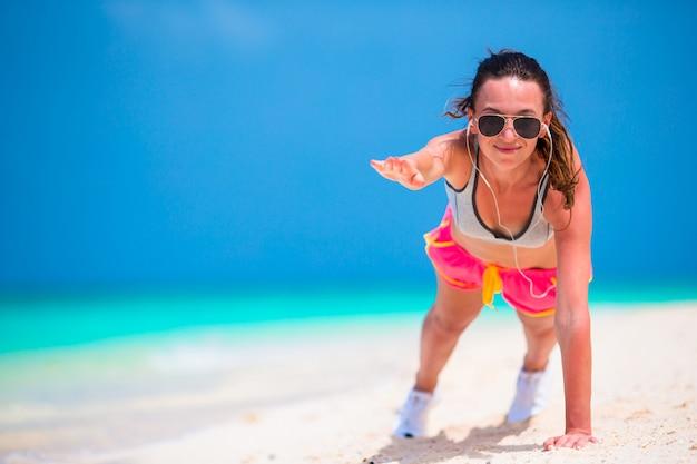 ビーチでプッシュアップ運動を行うフィットネス若い女性