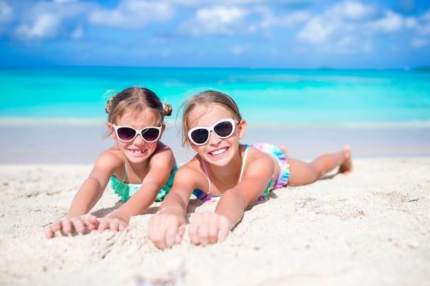 Закройте вверх по маленьким девочкам на песчаном пляже. счастливые дети лежат на теплом белом песке