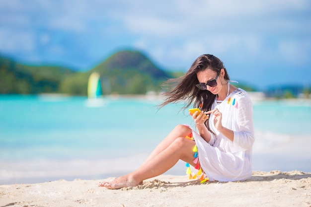 熱帯のビーチで携帯電話を持つ若い女性。カリブ海の島の携帯電話とビーチで美しい少女