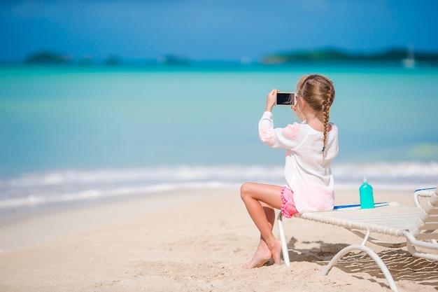 サンベッドの上に座って彼女のカメラでビデオや写真を作る少女