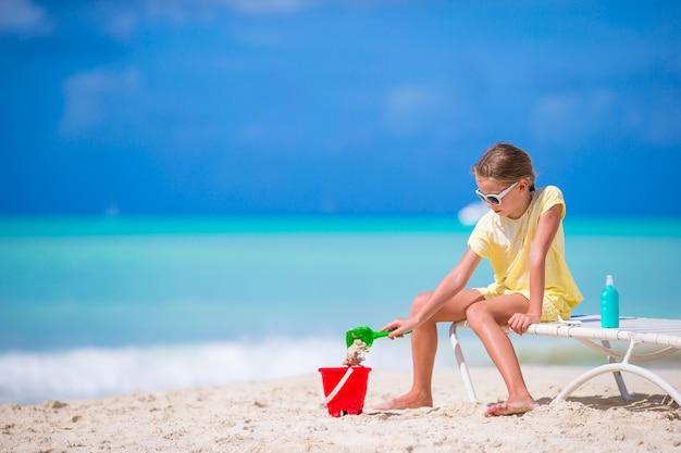Прелестная маленькая девочка играя с игрушками на каникулах пляжа. малыш играет с песком
