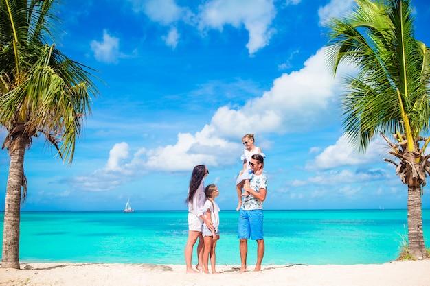 楽しんで白いビーチで幸せな美しい家族