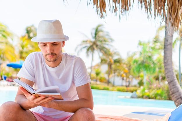 横になっている海岸の本を持つ男
