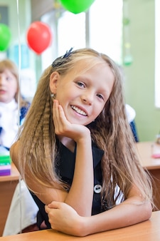 Очаровательная маленькая школьница в своем классе за столом