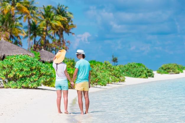 新婚旅行の熱帯の島でビーチの桟橋で若いカップル