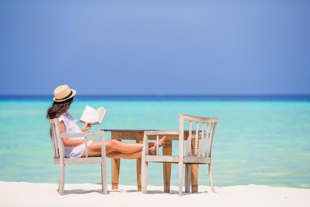 屋外ビーチカフェで読書の若い女性