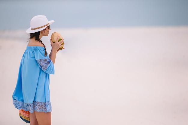 Молодая женщина пьет кокосовое молоко во время тропического отпуска