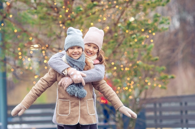冬の雪の日に屋外のアイススケート場でスケートのかわいい女の子