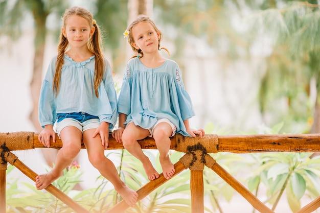 少し幸せな面白い女の子は、一緒に遊んで熱帯のビーチで多くの楽しみを持っています。晴れた日に雨が海に