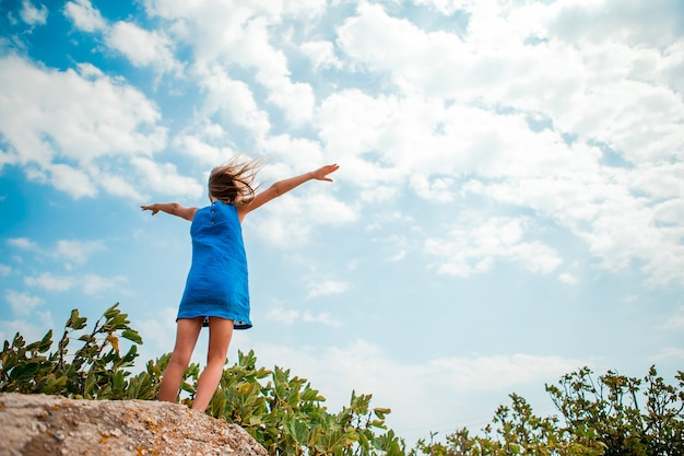ドレスの少女は幸せな空の景色を楽しんでいます